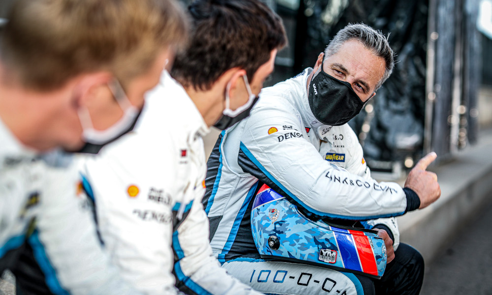 Yvan Muller wears a mask whilst talking to his team-mates