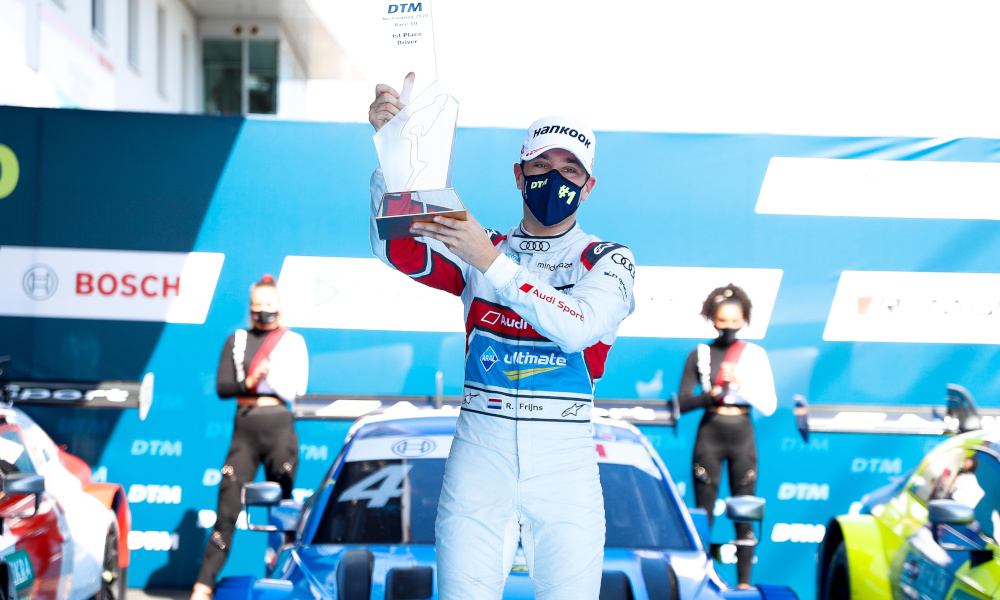 Robin Frijns celebrates with his trophy on the podium whilst wearing a mask
