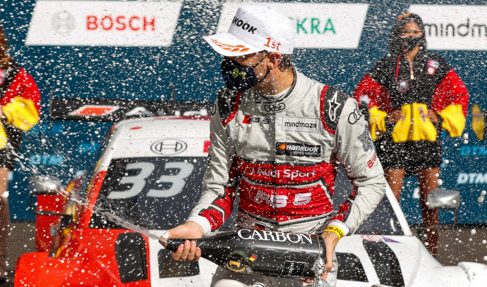 René Rast spraying champagne and wearing a mask