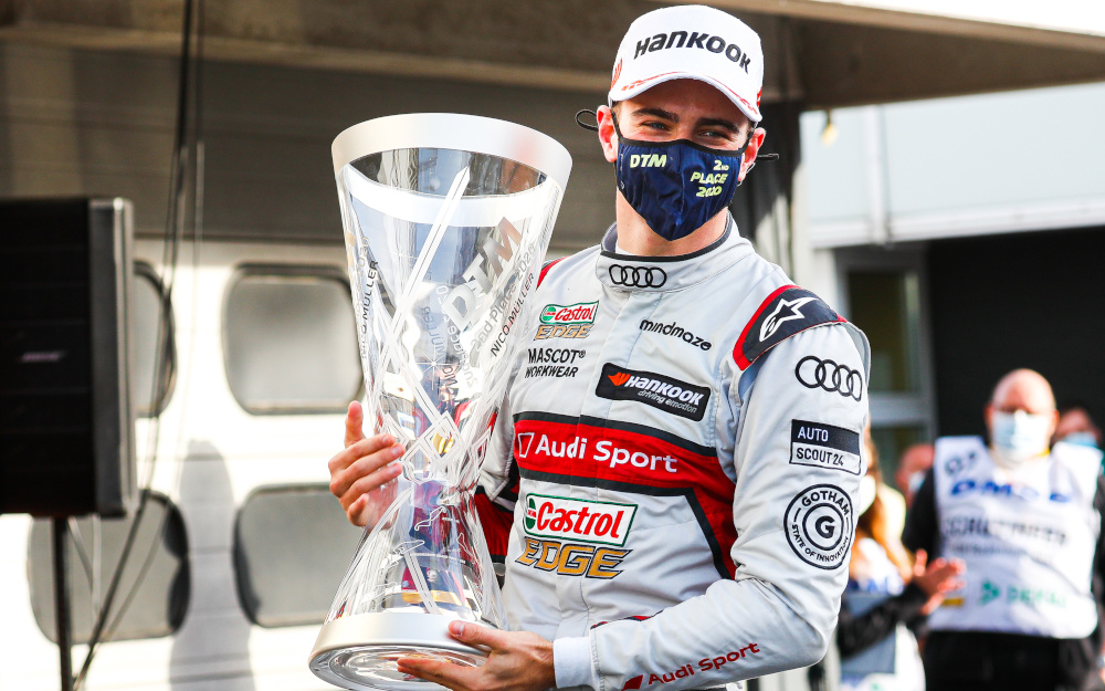 Nico Müller celebrates with his trophy whilst wearing a mask